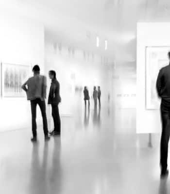Das Foto stellt Menschen in einer Kunstgalerie dar. Sie betrachten und kaufen vielleicht gerade ein Kunstwerk.